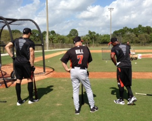 Giancarlo Stanton, Perry Hill and Juan Pierre stand around the batting cage.